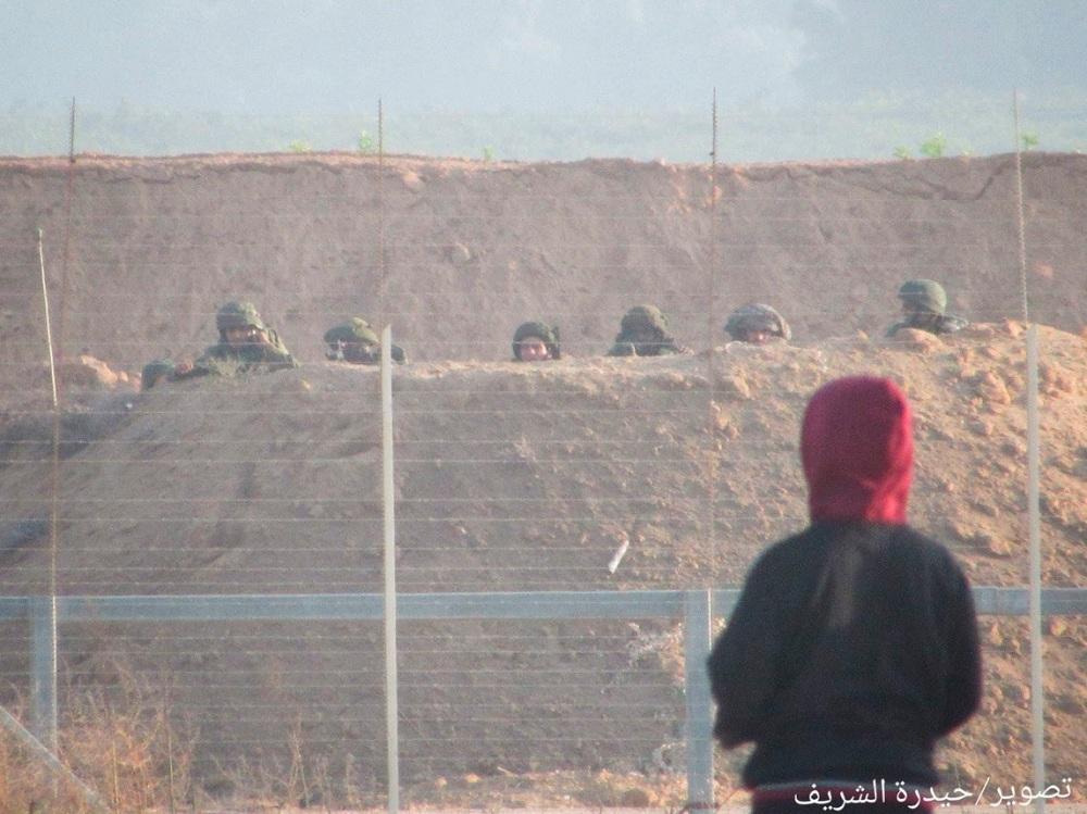 Gaza Zaun bei Khan Younis Soldaten dahinter jugendlicher Demonstrant davor