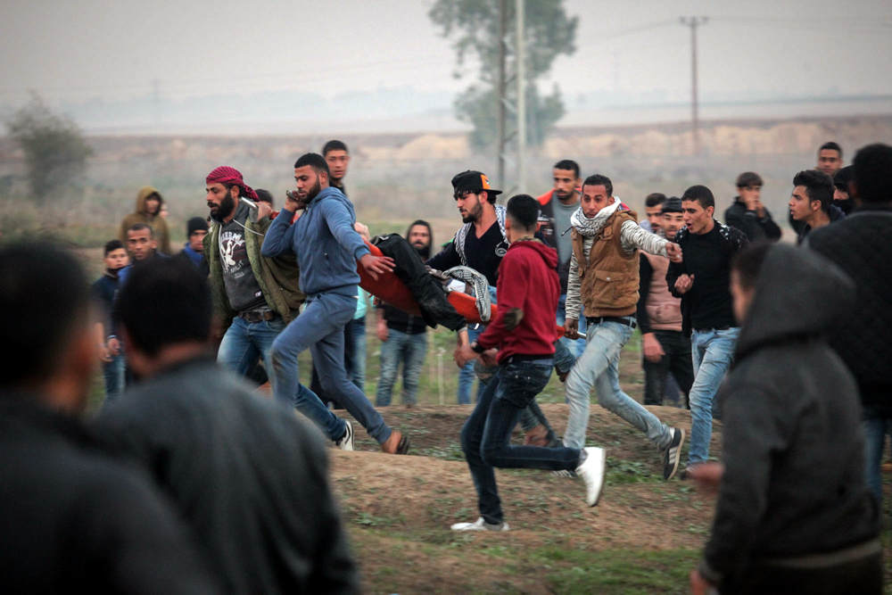 Palestinians carrying a wounded at Gaza border 29_12_20174