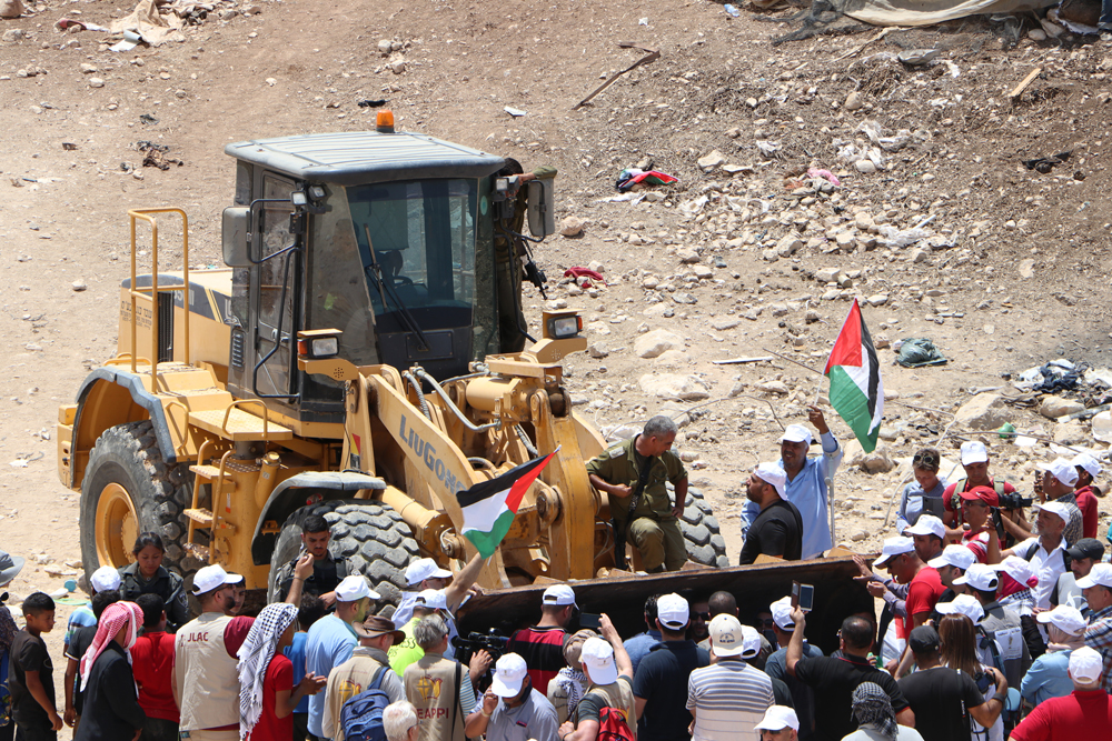 Bulldozer at Khan al-Ahmar with proteters WAFA.jpg