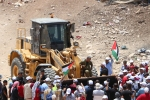 Bulldozer at Khan al-Ahmar with proteters WAFA